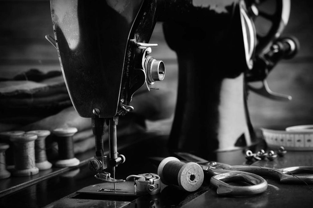 A sewing machine used for alterations and custom suits and shirts in a black and white color scheme