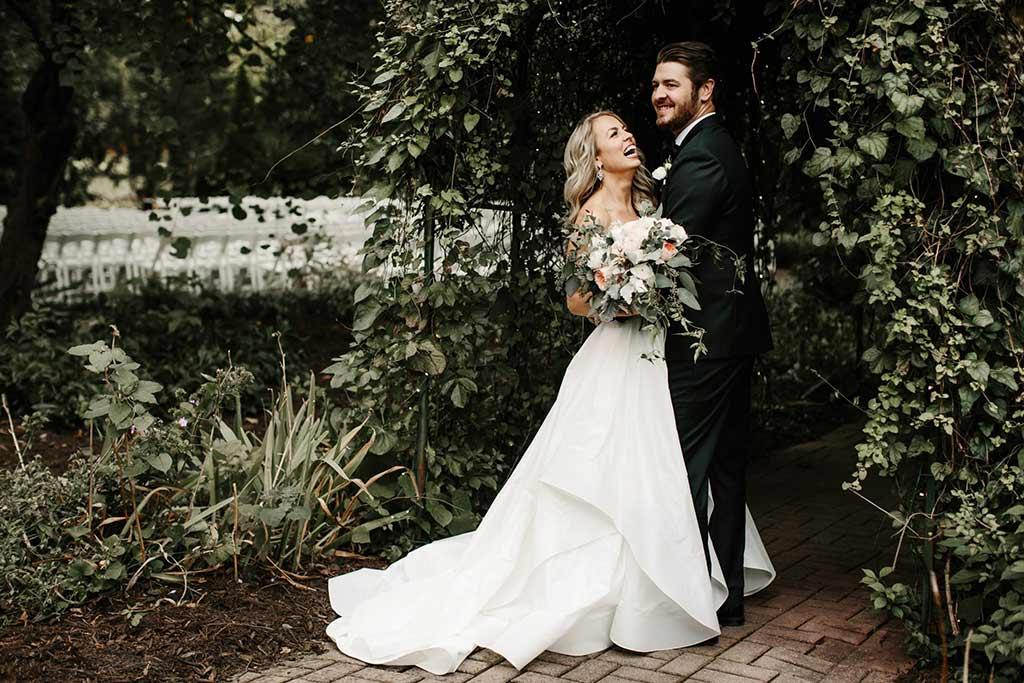 bride wearing custom altered wedding gown and groom wearing custom made tuxedo